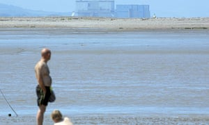 Holidaymakers at Burnham-on-Sea overlooked by Hinkley Point nuclear power station