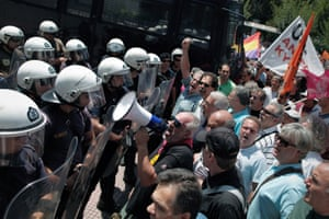 State school teachers shout slogans toward a riot police cordon securing the ministry of Administrative Reform during a protest against the austerity measures in central Athens on Tuesday, July 2, 2013.