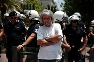 A teacher stands in front of policemen during a rally organised by the teachers unions, who are opposing reforms in their sector, in central Athens July 2, 2013