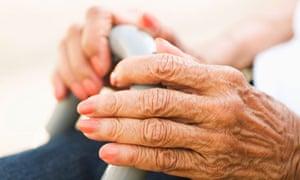 Hands of an elderly woman holding a cane