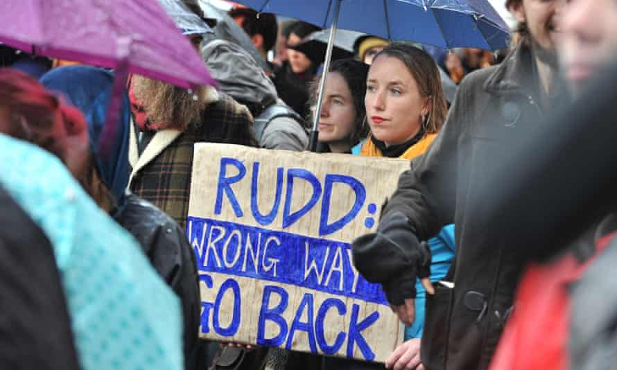 A protester holds a placard in the rain during a protest against the Australian Government asylum seeker policy in Melbourne on July 20, 2013.