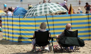 A couple sit under a sun shade on the beach in Weymouth