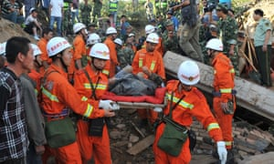 Rescuers carry an earthquake survivor to safety in Yongguang Village, Minxian County in northwest China. The death toll has climbed to 89 in the 6.6-magnitude earthquake on Monday morning.