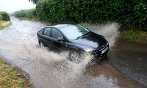 A car in Hatfield, Worcestershire, makes its way through flash floods after heavy thunderstorms