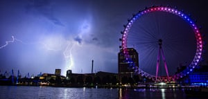 Stormy weather: Lightning strikes behind The London Eye in central London which is coloured