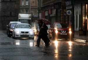 Stormy weather: A woman crosses the road during heavy rain in Glasgow, Scotland