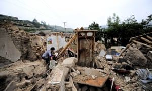 A woman gathers belongings from an earthquake-damaged home in Meichuan township in northwest China's Gansu province. Thousands of rescue personnel have been sent to help victims in the region though landslides and flooding have hampered their efforts.