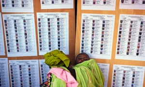 A woman carrying her baby searches for her name on a list of eligible voters at an election centre in Bamako. Mali is due to hold presidential elections on Sunday.