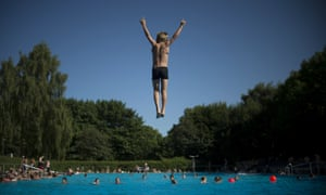 A little boy jumps into a public swimming pool in Berlin's Neukoelln district as temperatures in the capital reached 30 degrees celsius.