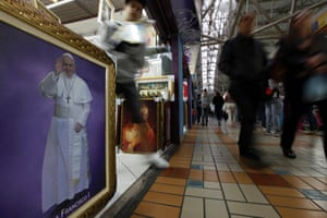 People walk past an image of Pope Francis displayed in a store close to the Basilica of the National Shrine of Our Lady in Aparecida do Norte. Pope Francis will visit the basilica on July 24. Photograph: Paulo Whitaker/Reuters