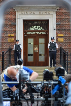 Police personnel guard the door to the Lindo Wing of St Mary's Hospital in London.