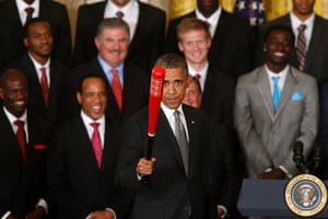 President Barack Obama holds up a Louisville Slugger baseball bat presented to him by Louisville basketball coach Rick Pitino as he honored the 2013 NCAA Men s Basketball Champions, the Louisville Cardinals in the East Room at the White House in Washington. Photograph: Charles Dharapak/AP