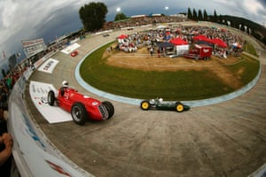 A fisheye lens photo of Peter Studer (R) driving his 1962 Lotus 24 Formula One race car ahead of Georg Kaufmann (L) on a 1958 Maserati 250 F through a steep turn during the Indianapolis in Oerlikon race demonstration at the Offene Rennbahn cycling track in Zurich. Photograph: Arnd Wiegmann/Reuters