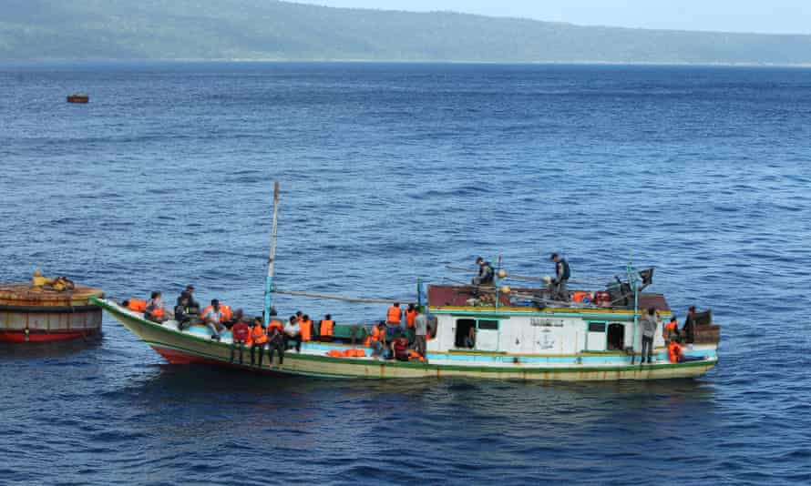 Asylum seekers are escorted to Smiths Point on Christmas Island, 2,600km northwest of Perth after being intercepted by Australian customs and border protection service officers.