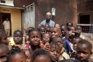 Mohamed Alakama Doumbouya with a large group of children, in Guinea