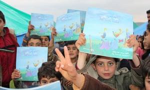 Syrian refugees holding up Samah Zaitoun's book Far From Home.