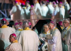 Pope in Brazil: Bishops wearing plastic rain hoods attend the World Youth Day inaugural Mas