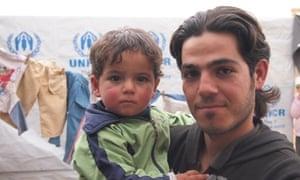 Hasan Hariri, 24, with his son Diya in Zaatari refugee camp, Jordan.