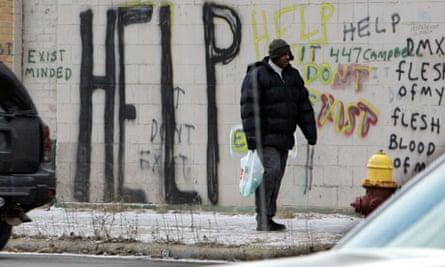 Pedestrian walking past graffiti in downtown Detroit