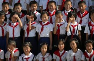North Korea 60th: North Korean schoolchildren rub their eyes facing the sun while getting the