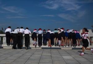 North Korea 60th: North Korean school children lean over a foot bridge to see carp swimming i