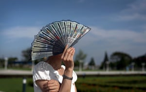 North Korea 60th: A guide shields her face from the sun while touring the park surrounding Ku