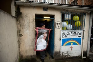 Pope in Brazil: A woman poses with a poster of Pope Francis outside her home before the Pop