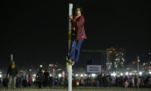 Pope Brazil updated: A woman watches from a pole as Pope Francis celebrates Mass