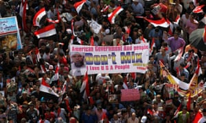 Egyptian protesters hold a banner with a caricature of US president Barack Obama with a turban and a beard, at Tahrir square, Cairo, Egypt.