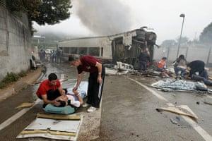20 Photos: 2 men comfort a woman next to a derailed car near Santiago de Compostela