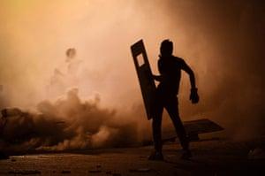 20 Photos: A Bahraini protester stands amidst tear