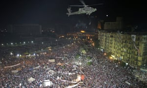 An Egyptian army Apache helicopter flies over Tahrir square during a protest in support of the Egyptian armed forces, in Cairo