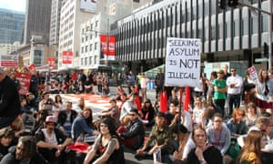 Protesters sit down in front of Sydney Town Hall.