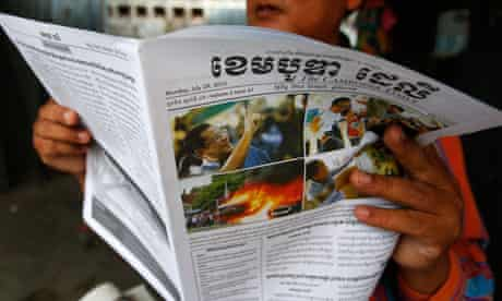 A man reads newspaper coverage about the elections