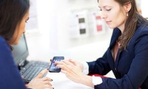 Shop assistant helping a customer choosing a smartphone