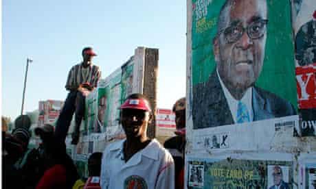 Zimbabweans walk past a poster for President Robert Mugabe in Chinhoyi