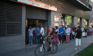 A man cycles past a queue of people waiting to enter an unemployment registry office in Madrid, Spain Thursday July 25, 2013.