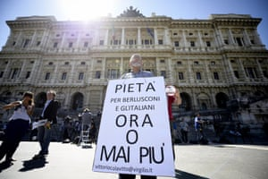A man holds a placard in support of former Italian prime minister Silvio Berlusconi in front of the Court of Cassation building in central Rome, Italy, 31 July 2013. The placard reads 'Pity for Berlusconi and Italians, now or never''