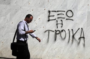"""A man walks past a wall of a Bank of Cyprus branch, which has graffiti on it reading in Greek: """"Troika get out"""" in the capital, Nicosia, on July 30, 2013."""
