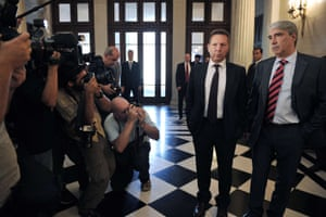 Photographers take pictures of  Greek Finance minister Yiannis Stournaras (L) talking with government's spokesman, Simos Kedikoglou at the primae minister's office in Athens on July 4, 2013.