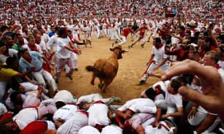 A bull jumps over revelers in a bullring during the Running of the Bulls, in Pamplona