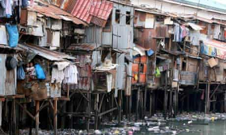 A row of shanties hangs precariously over a filthy river full of rubbish