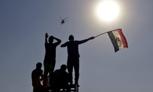 Egyptians wave their national flag as an army helicopter flies by, one day after the announcement made by the Egyptian Defense Minister Abdel-Fattah Al-Sissi of a presidential handover in Egypt, in Tahrir square.