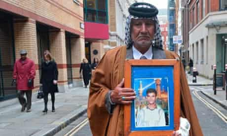 Mizal Karim al-Sweady holds a photograph of his dead son, Hamid al-Sweady