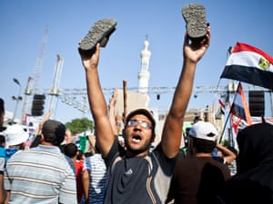 A supporter of ousted Egypt's President Mohammed Morsi reacts as an military helicopter flies over during a rally in Nasr City,Cairo.