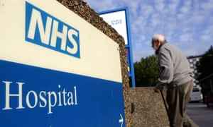 An older man walks past an NHS hospital sign
