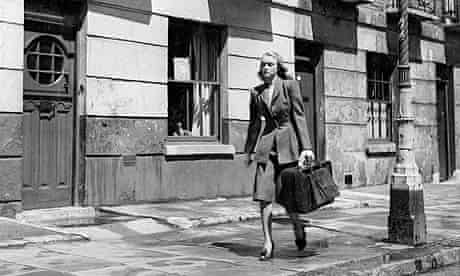 Black and white shot of woman walking down the street with suitcase