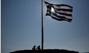 Tourists rest beneath a Greek flag atop the hill of the Acropolis in Athens