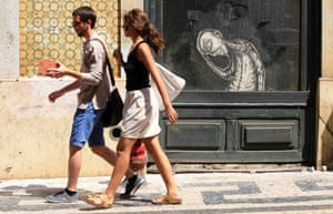 A couple walks past a closed shop in downtown Lisbon July 5, 2013