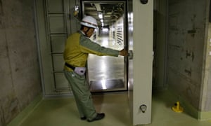 A worker opens the watertight door at Chubu Electric Power Company's Hamaoka nuclear power station